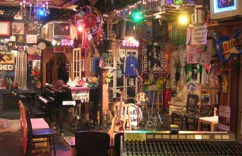 Photo of interior of Kulak's Woodshed view from front door of mixing board, stage area with piano and drum kit and decorations