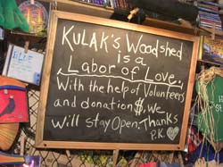 Photo of chalkboard on which is written: Kulak's Woodshed is a labor of love - with the help of volunteers and donation $ we will stay open - thanks - P K